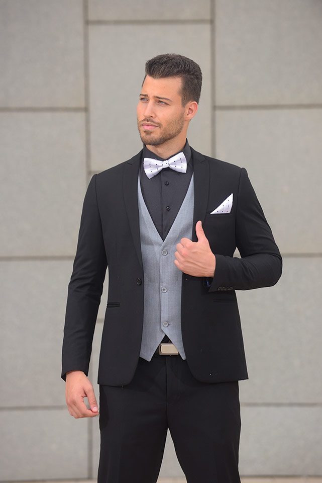 חליפת חתן שחורה מעוצבת עם וסט אפור ופפיון לבן